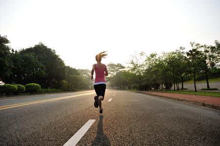 one female: Runner athlete running at road. woman fitness sunrise jogging workout wellness concept.