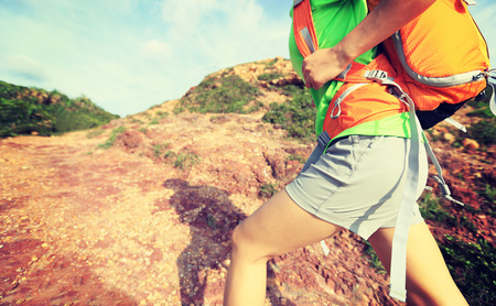 retros: young woman backpacker climbing on mountain trail Stock Photo