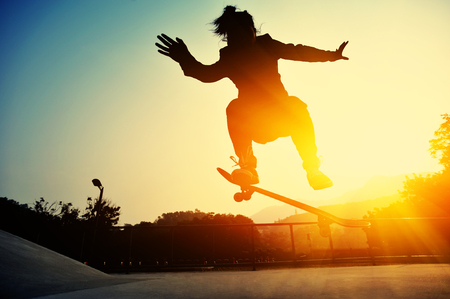 skateboard shoes: young girl skateboarding at sunrise skate park Stock Photo