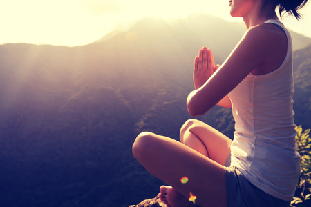 young yoga woman at sunrise mountain peak Stockfoto