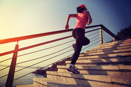 of stone: healthy lifestyle sports woman running up on stone stairs sunrise seaside