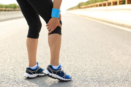 leg pain: woman runner hold her injured leg Stock Photo