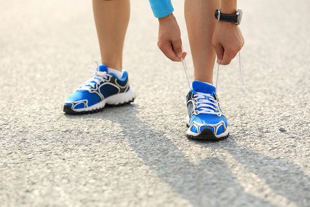 shoelaces: young woman runner tying shoelaces on city road