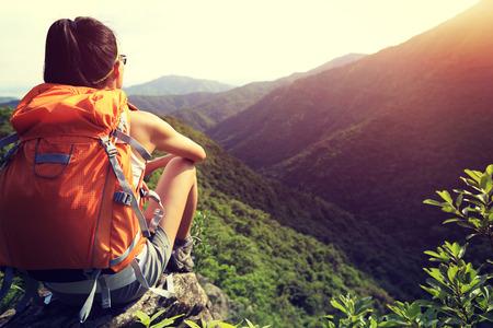 Frau Backpacker den Blick auf Sonnenaufgang Berggipfel Klippe Fels genießen sitzen