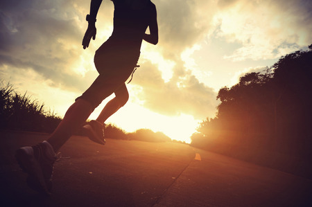 Runner athlete running at seaside road. woman fitness silhouette sunrise jogging workout wellness concept. Banque d'images