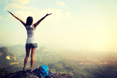 cheering woman hiker open arms at mountain peak Standard-Bild
