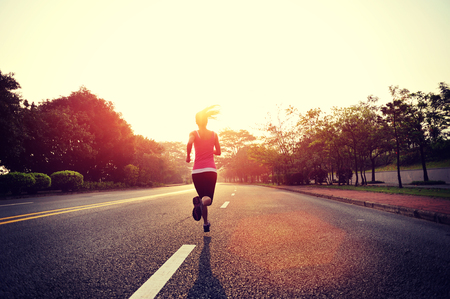free running: Young woman running at road during sunrise Stock Photo