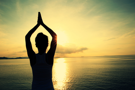 beach yoga: healthy yoga woman meditation at sunrise seaside Stock Photo