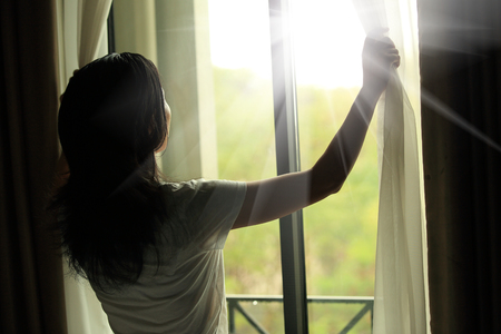 curtain window: girl opening curtains in a bedroom