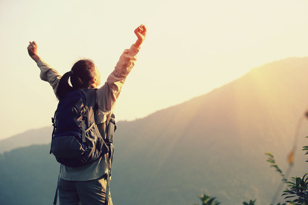 freedom woman: cheering woman hiker open arms at mountain peak Stock Photo