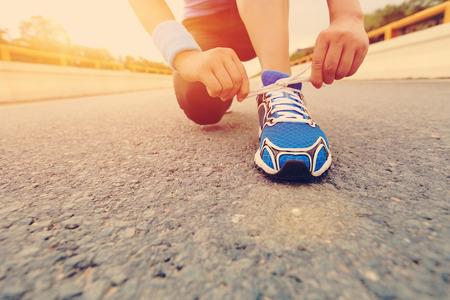 young woman runner tying shoelaces on sunrise birdge road Standard-Bild