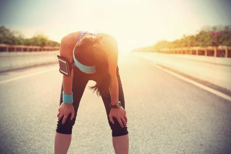 sudando: Corredor de la mujer cansada de tomar un descanso después de correr duro en el camino de ciudad