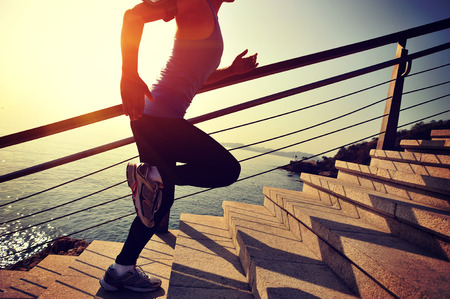 active listening: healthy lifestyle sports woman running up on stone stairs sunrise seaside