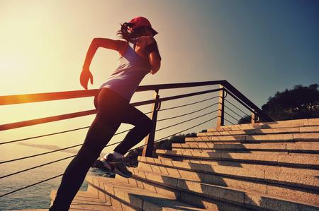 atleta corriendo: mujer sana de los deportes de estilo de vida con procesamiento de escaleras de piedra junto al mar salida del sol Foto de archivo