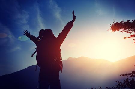 cheering woman hiker open arms at mountain peak Foto de archivo