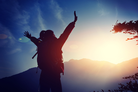 backpackers: cheering woman hiker open arms at mountain peak Stock Photo
