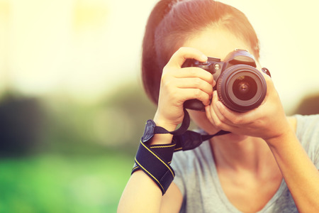 retro woman: young woman photographer taking photo outdoor Stock Photo