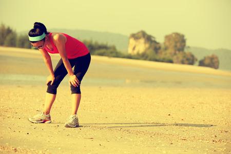 sediento: mujer cansada después de correr duro en la playa Foto de archivo