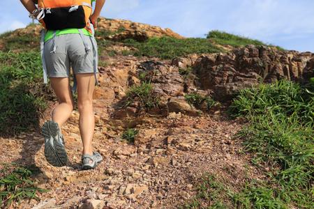 sandal tree: young woman backpacker climbing to mountain peak Stock Photo