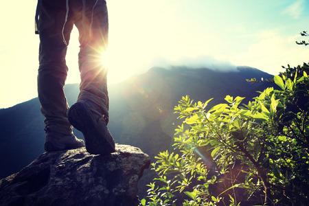 hiking: woman hiker legs climbing on sunrise mountain peak rock
