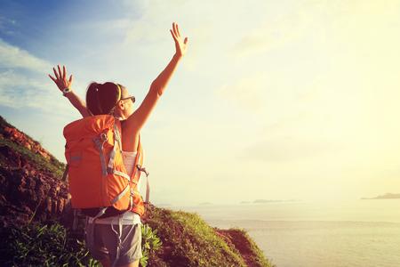 mochila de viaje: animando los brazos abiertos Mujer del caminante en la montaña de la salida del sol junto al mar
