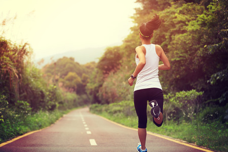 atleta: joven mujer de fitness corredor ejecutan en la pista