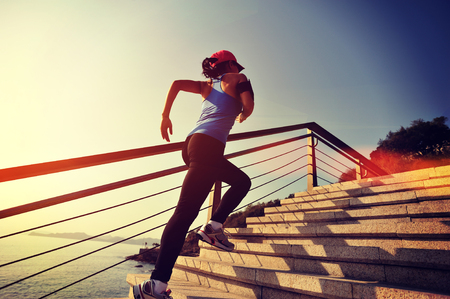young girl: healthy lifestyle sports woman running up on stone stairs sunrise seaside