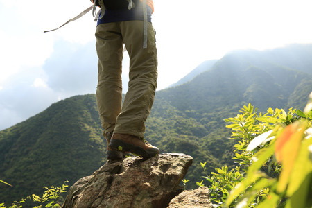hiking boots: woman hiker legs climbing on mountain peak rock