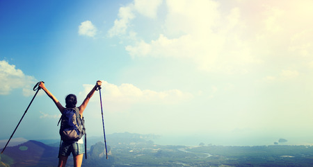 red mountain open space: cheering woman hiker open arms at mountain peak Stock Photo