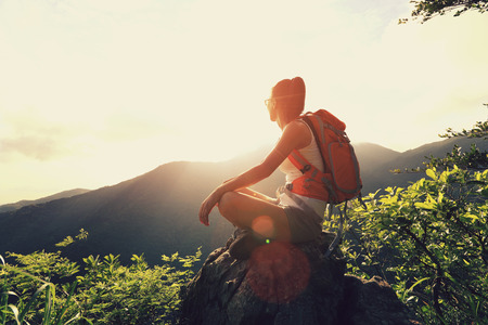 backpack: woman backpacker sit on sunrise mountain peak cliff rock enjoy the view