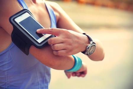 coureur: Runner athl�te �couter de la musique de t�l�phone intelligent lecteur mp3 t�l�phone intelligent armband.woman concept de remise en forme de jogging s�ance d'entra�nement de bien-�tre.
