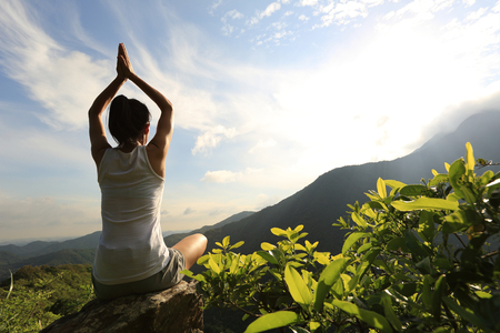woman outdoor: young yoga woman at sunrise mountain peak Stock Photo