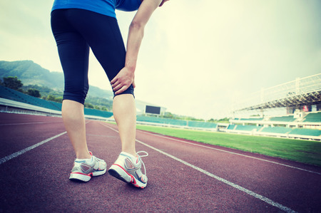 muscle spasm: woman runner hold her injured leg on track