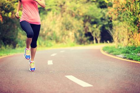 personas corriendo: j�venes piernas de la mujer de la aptitud que se ejecutan en la pista forestal Foto de archivo