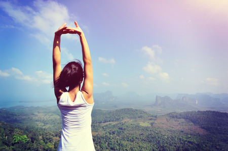 young woman stretching arms at mountain peak Stock Photo
