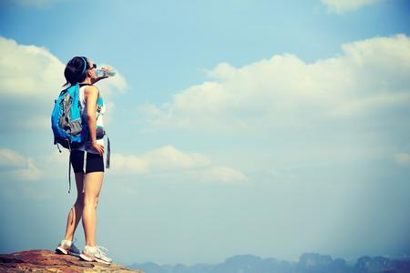 tomando agua: caminante de la mujer beber agua en el pico acantilado de la montaña Foto de archivo