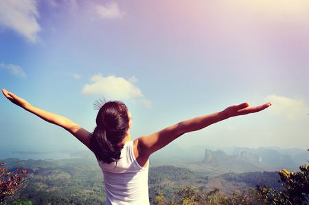 Mujer joven que anima los brazos abiertos en el pico de la montaña