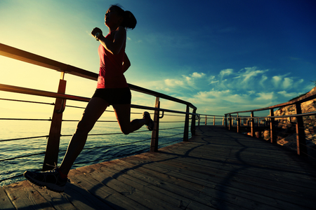 active woman: healthy lifestyle sports woman running on wooden boardwalk sunrise seaside