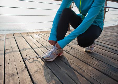 shoelace: woman runner tying shoelace on wooden boardwalk