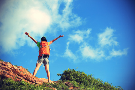 female: cheering young woman backpacker enjoy the view at mountain peak Stock Photo