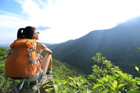 green back: young woman hiker enjoy the view on mountain peak cliff