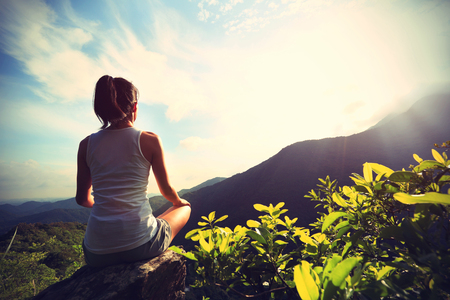 young yoga woman at sunrise mountain peak Stock Photo