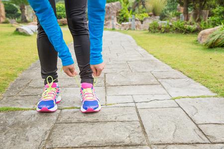 shoelace: young asian woman tying shoelace