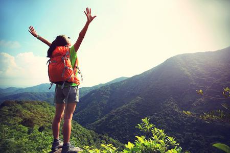 山ピークの崖での応援の女性ハイカー オープンアームズ
