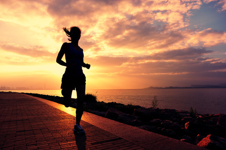 female silhouette: Runner athlete running at seaside. woman fitness silhouette sunrise jogging workout wellness concept.