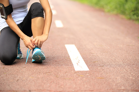 shoelaces: young woman runner tying shoelaces