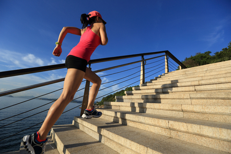 stone stairs: healthy lifestyle sports woman running up on stone stairs seaside