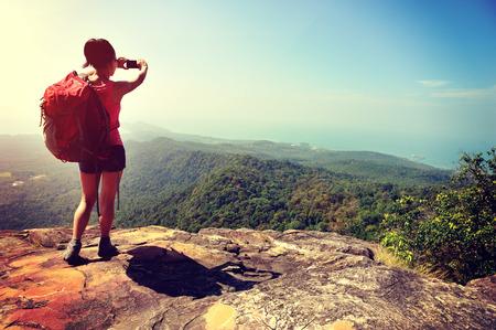 hiking: woman hiker taking photo with digital camera at mountain peak cliff