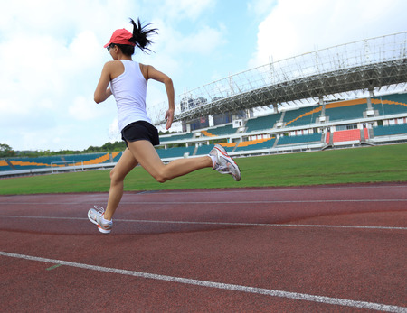 sombrero: young fitness woman runner running on track