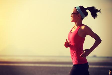 niñas chinas: joven mujer de estilo de vida saludable corriendo en la playa de la salida del sol